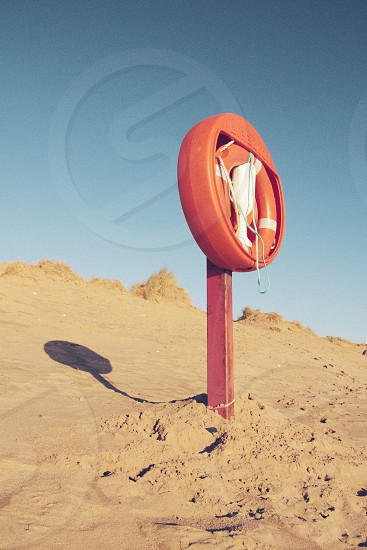 A lifebuoy sticks out of the sand on Exmouth beach on a perfect sunny blue sky day. photo