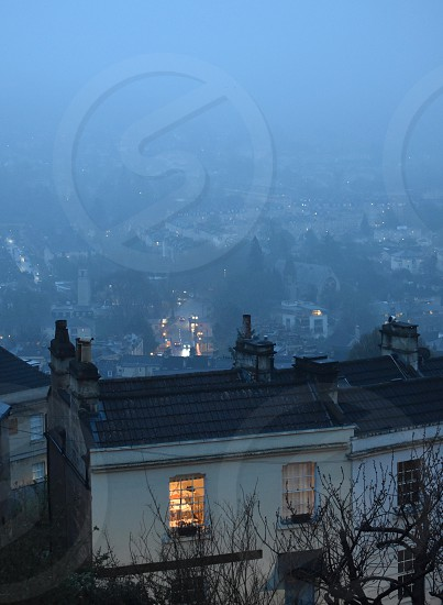 View over roof tops to blue misty landscape beyond. The puddles on the road in the distance  reflect the headlights of the cars. photo