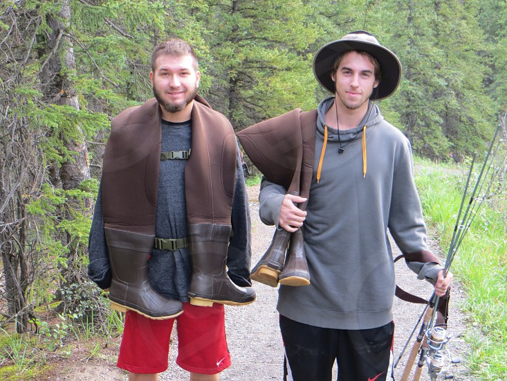 photography of two men carrying fisher waders photo