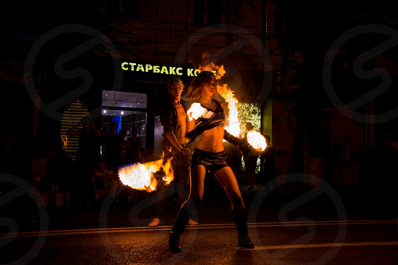 woman in black leather outfit fire dancing photo