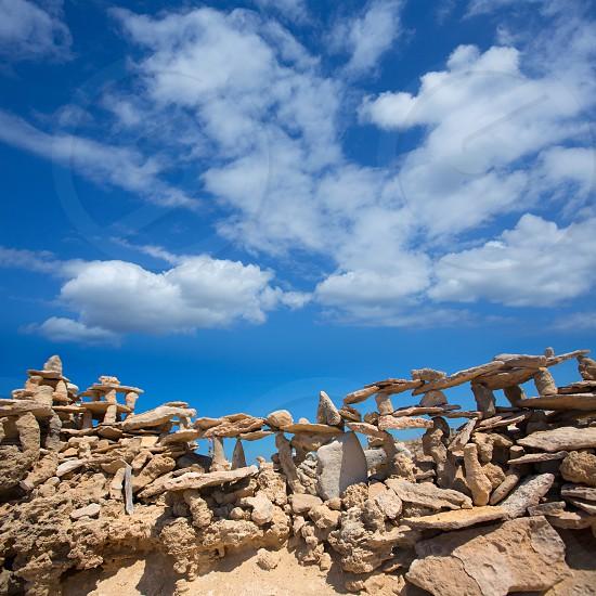 Stone figures on beach shore of Illetes beach in Formentera Mediterranean Balearic Islands photo