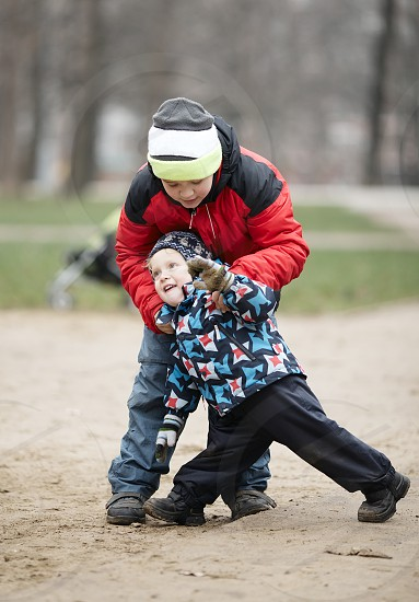 Two young brothers playing outdoors in a park in winter wrestling with each other as they enjoy their freedom photo