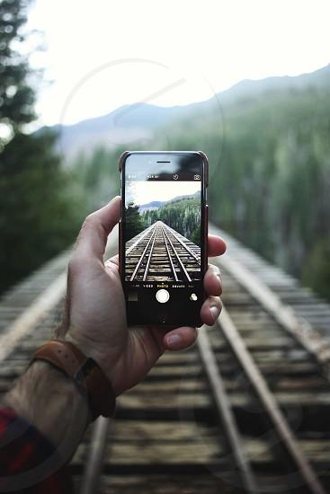 person taking picture of railroad tracks photo