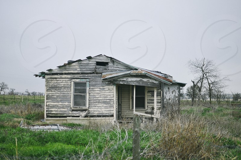 white wooden abandoned house in middle of grass field photo