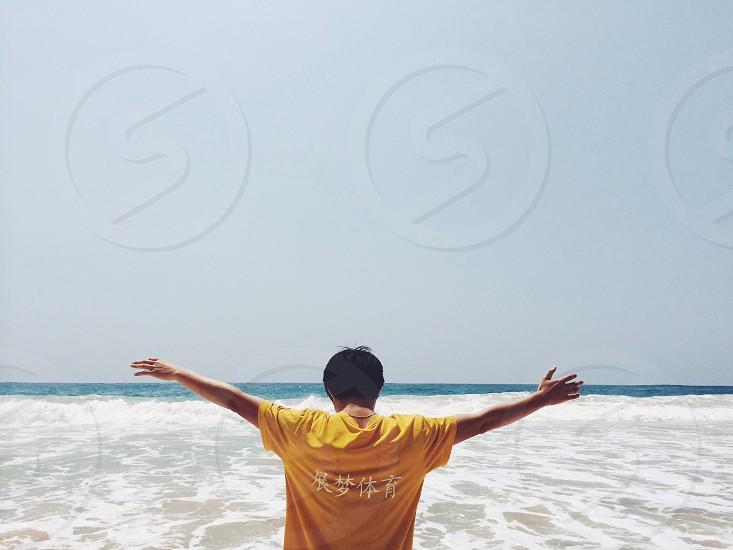 man in yellow shirt standing photo
