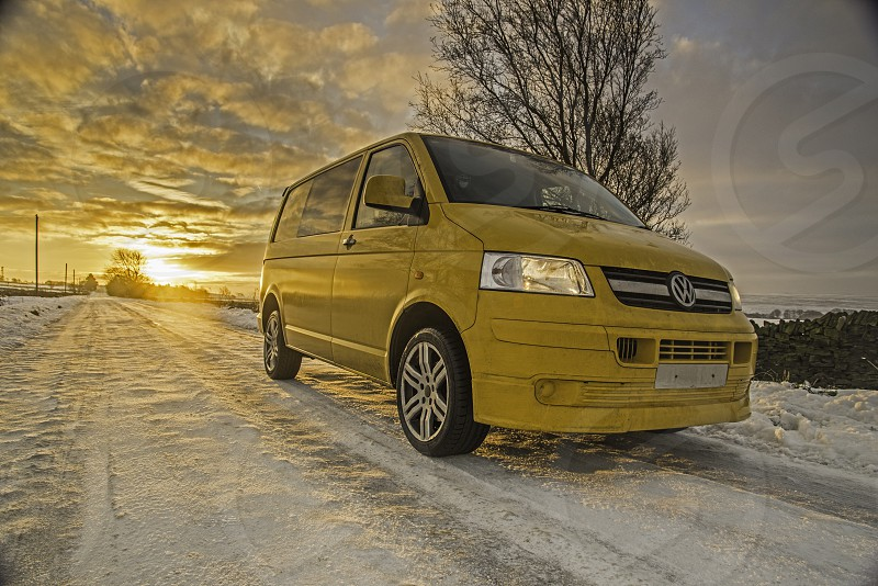 Yellow VW Transporter with a sunrise behind. photo