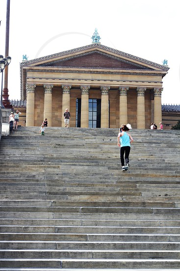 woman in mint racerback tank top running up monument steps photo