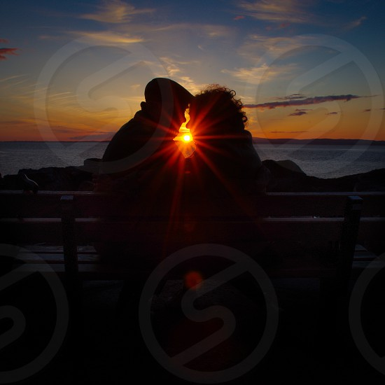 Elderly couple sat on bench by the coast in silhouette at sunset with sunburst photo