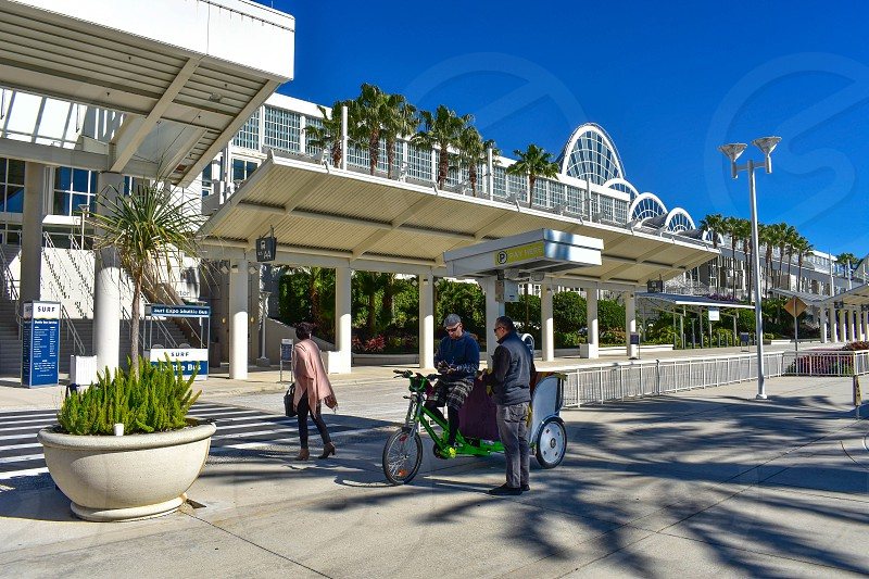 Orlando Florida. January 12 2019. Person paying for rickshaw pedal taxi ride in the International Drive area (3) photo