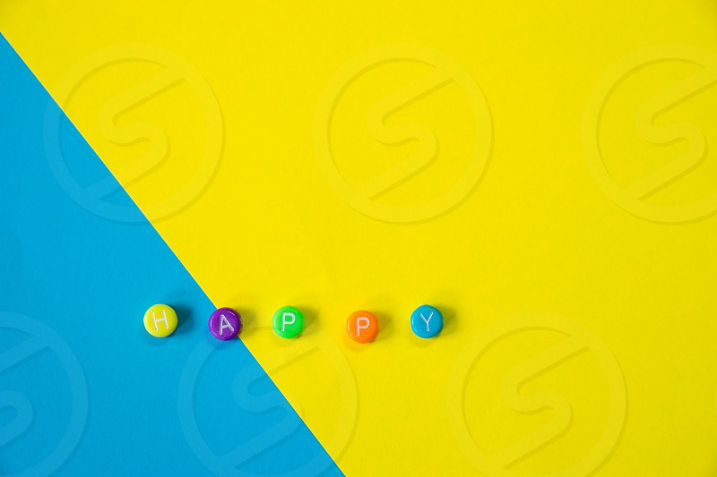 Colourful Happy word alphabet letters on two vivid colur yellow and blue background photo