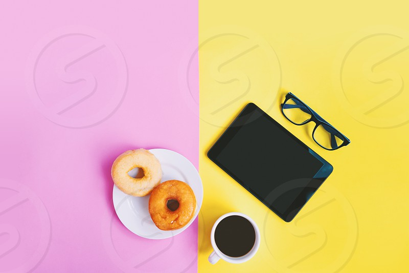 Modern working space of home office A cup of coffee donuts eyeglasses and tablet on yellow pink pastel background with copy space photo
