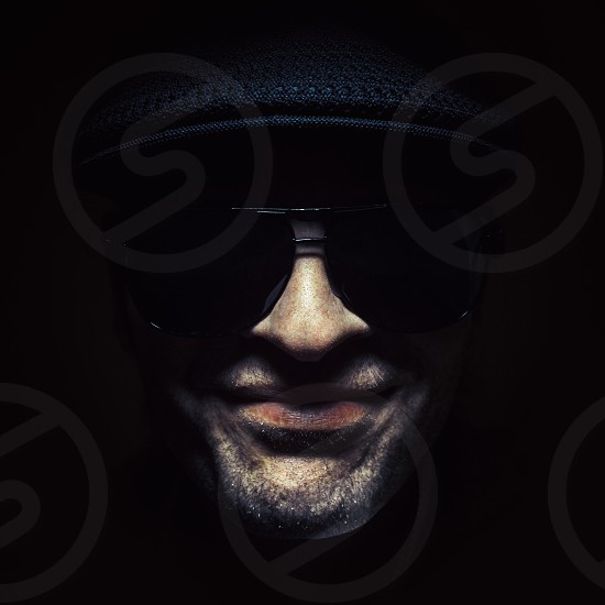 Just a portrait of a man playing an electric guitar wearing a hat and sun glasses.  photo