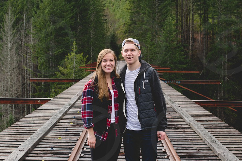 man and woman with blonde hair in coats smiling on railroad tracks photo