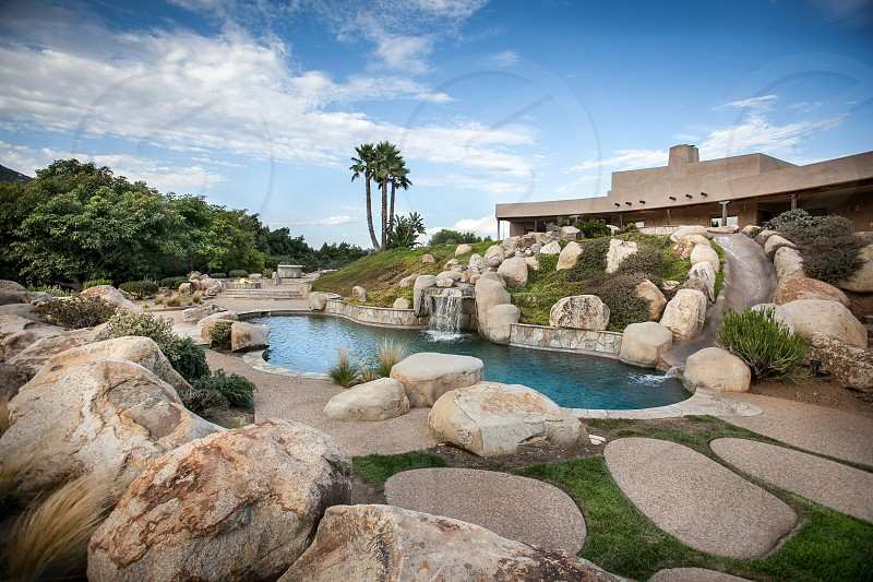 A luxury southern California backyard. Pool waterfall slide boulders grass palm trees pavers fire pit barbecue bbq. photo