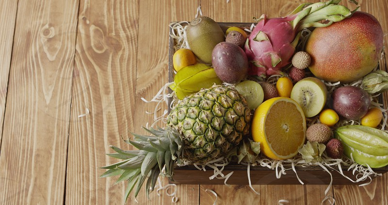 Box with assortment of freshly picked natural exotic fruits -ananas passion fruit mango on a wood shaving on a wooden background. Panoramic slow motion 4K UHD video 3840 2160p. Top view. photo