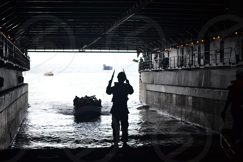 Navy Crewman Directs Boat Into Well Deck Of Amphibious Ship  photo