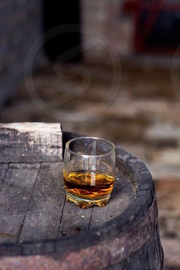 Glass of whiskey on wooden barrel in distillery photo