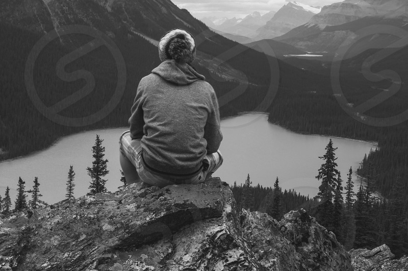 grayscale photo ofsitting person on rock in front of body of water photo
