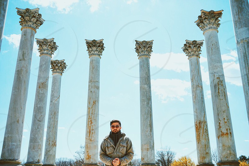 man in grey jacket standing beside concrete columns under blue sky during daytime photo