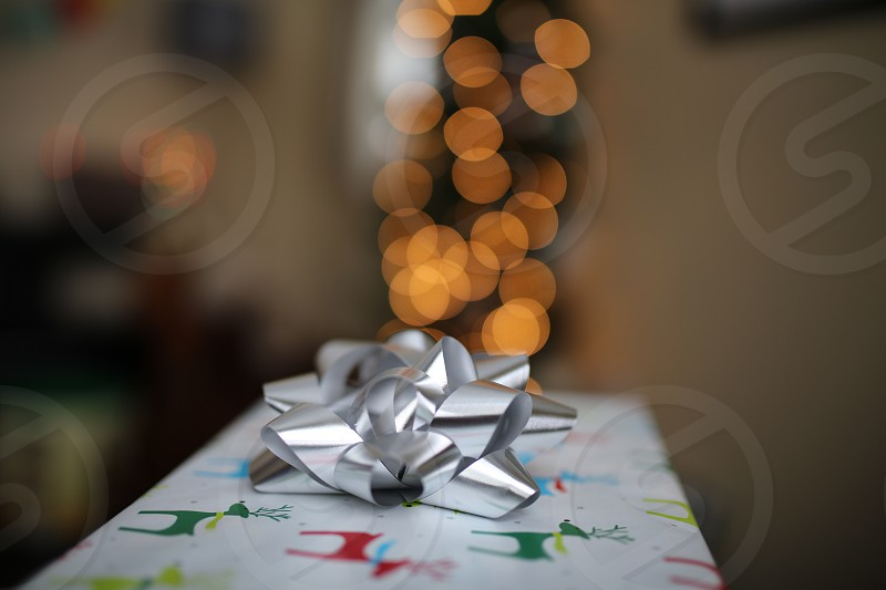 A Christmas gift with a blurry Christmas tree in background. photo