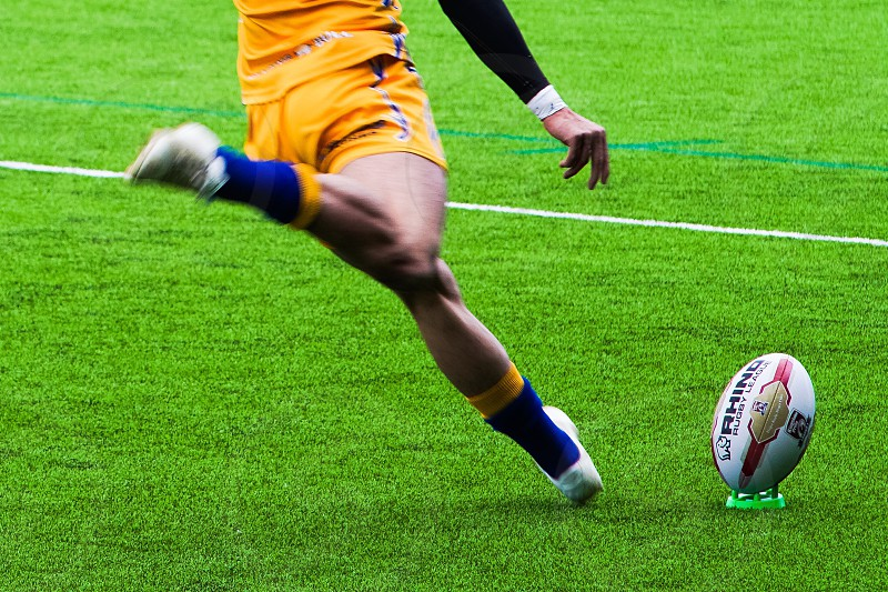 Rugby player about to kick ball photo