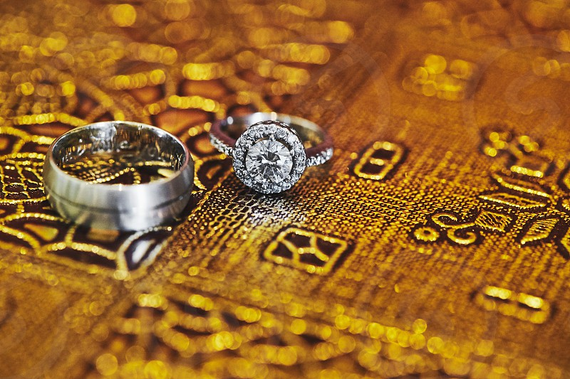The close-up shot of the engagement rings of the bride and groom focused on the diamond ring of the bride with glitter and shiny close-up photo