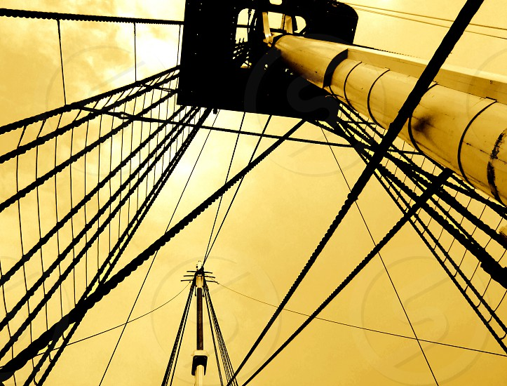 Looking up through ropes and ladders to the top of a ship's mast against a golden background. photo