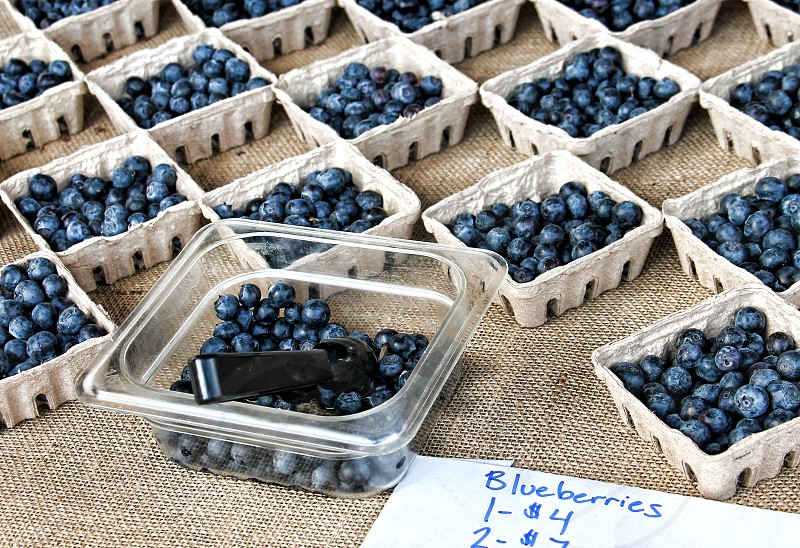 Boxes of blueberries for sale on a burlap cloth; one container open for taste testing at a farmer's market. photo