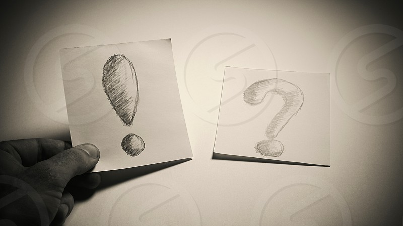 Exclamation and question signs drawn on paper male hand is choosing a paper with exclamation conceptual composition about having an idea or solution.  photo