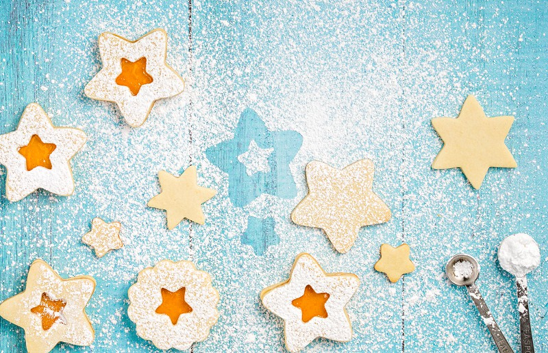 Christmas Linzer suger cookies with Orange apricot jam and icing sugar on a blue background. photo