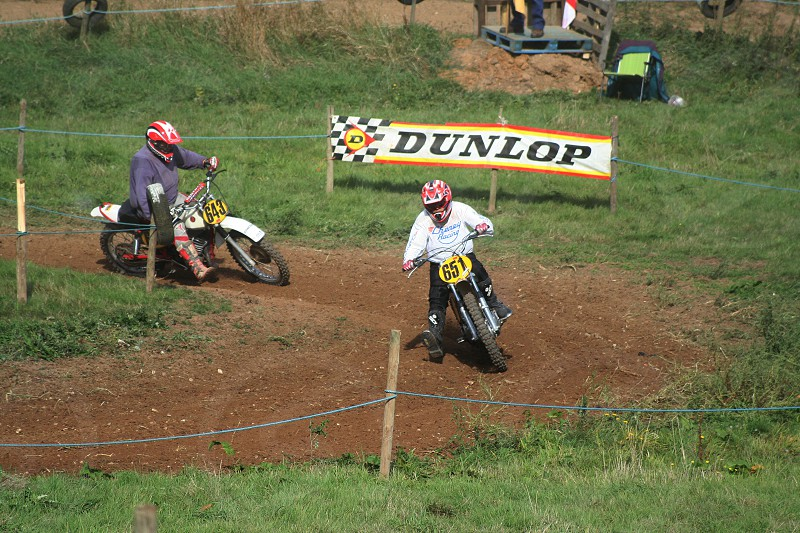 two people riding yellow and white dirt bikes on track near dunlop sign during daytime photo
