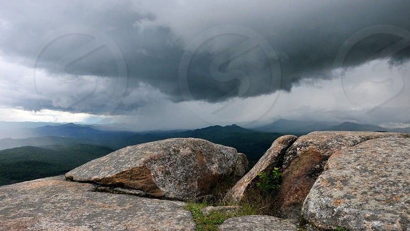 Storm clouds from the top o a mountain in the Adirondacks with sun peeking through. photo