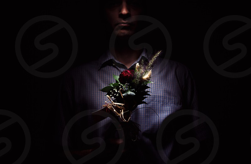 Lonely man with flowers in dark.  photo