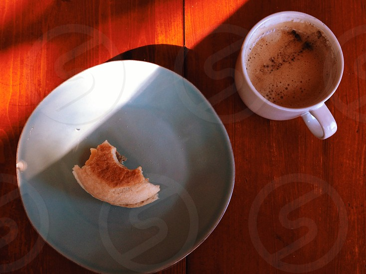 piece of bagel on plate and mug of beverage photo