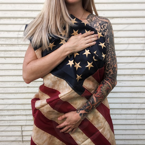 woman with sleeve tattoo covering herself with u.s.a flag standing against beige wall photo