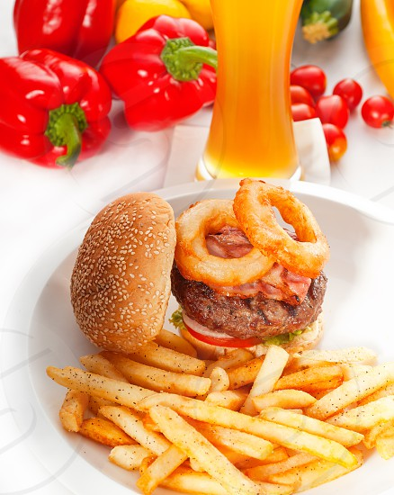 classic american hamburger sandwich with onion rings and french friesglass of  beer and fresh vegetables on background  MORE DELICIOUS FOOD ON PORTFOLIO photo