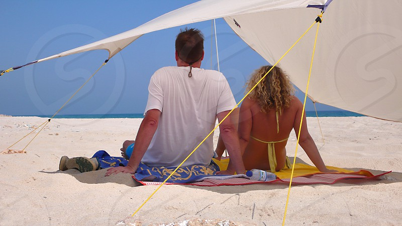 man and woman sitting under shade in beach photo