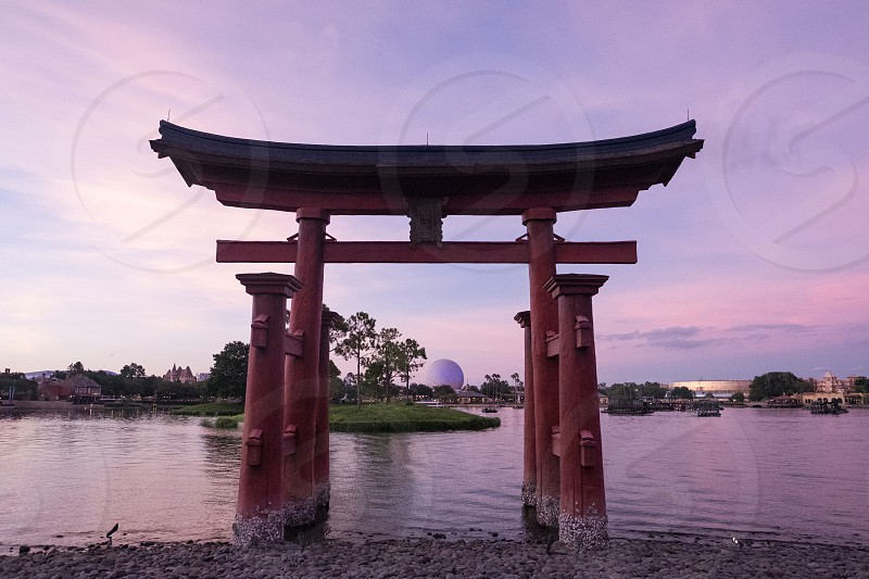 red torii gate on the body of water under sky with thin clouds during golden hours photo