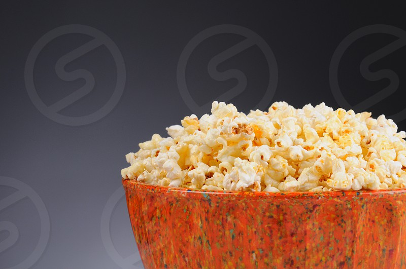 Closeup of a Bowl Full of Popcorn on a light to dark gray background. Horizontal format with copy space. photo