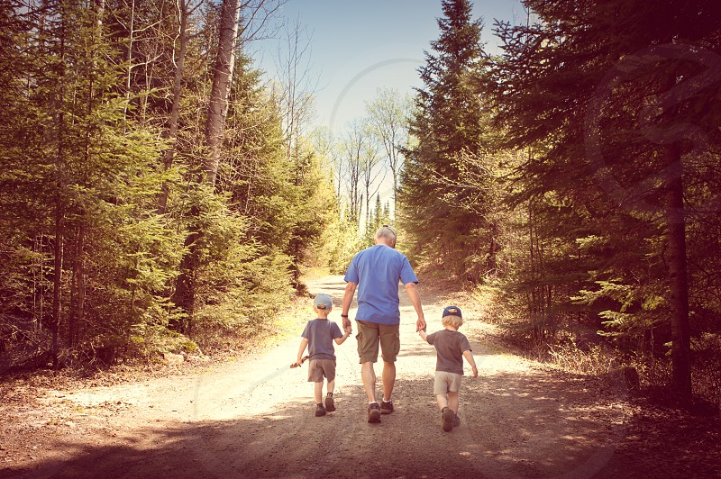 authentic travel generations grandpa grandkids boys children holding hands woods forest trees gravel kids hats walking road photo
