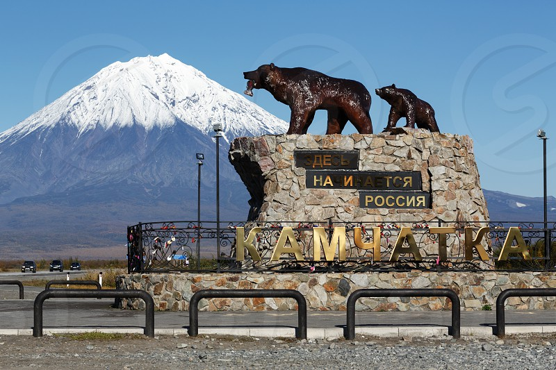 "YELIZOVO CITY KAMCHATKA PENINSULA RUSSIA - SEP 24 2017: Sculpture composition of Kamchatka brown bear family ""She-bear with teddy bear"" inscription: ""Here begins Russia. Kamchatka"" on background of Koryak Volcano. photo"