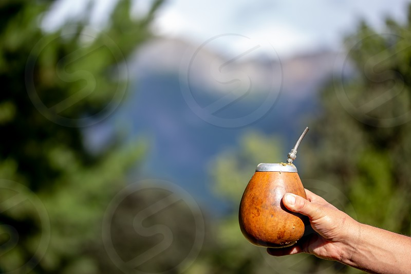 Man holding calabash yerba mate in nature. Travel and adventure concept. Latin American drink yerba mate. photo