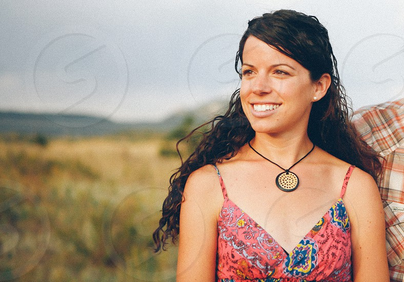 woman wearing a red blue and yellow floral summer dress and a black and white necklace photo