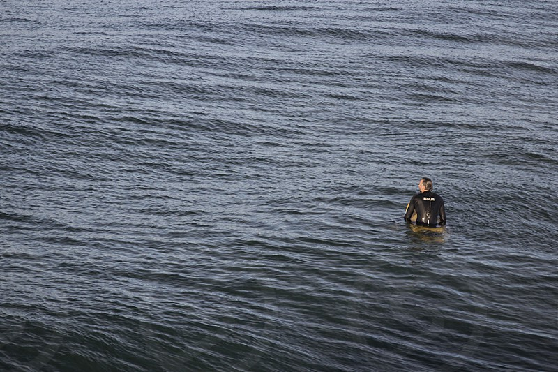 man in wetsuit paddling on surfboard photo
