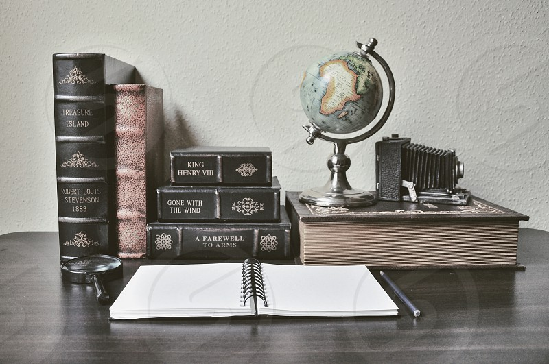 hardbound books notebook pen table globe and antique camera on table photo