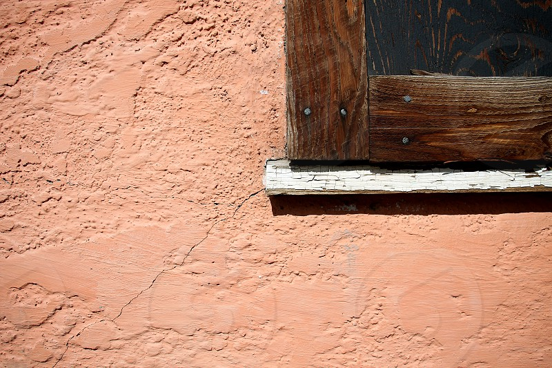 Detail shot of a corner of a wooden framed window on a light orange stucco wall. photo