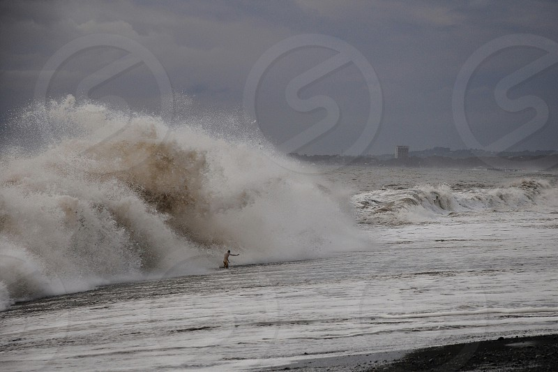 person doing surfing near water waves photo