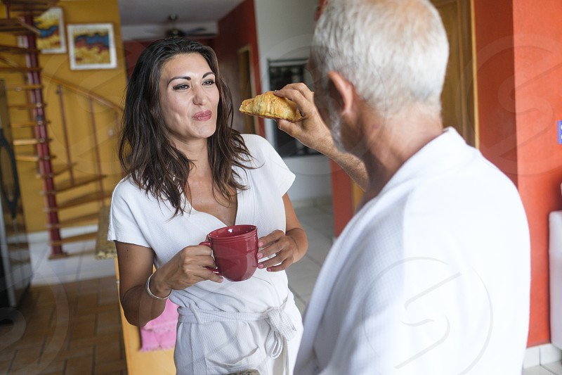 Breakfast of unequal couple - older man feeding a croissant to younger woman Nuevo Vallarta Nayarit Mexico photo