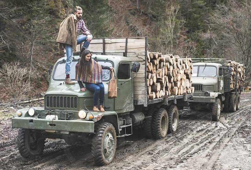 Young man and girl on truck with logs in the forest photo