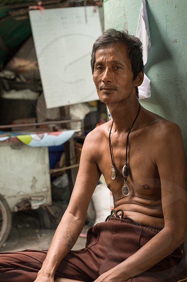 Photograph of a thin tall Thai man wearing Buddhist amulets in Bangkok Thailand on November 2017. photo